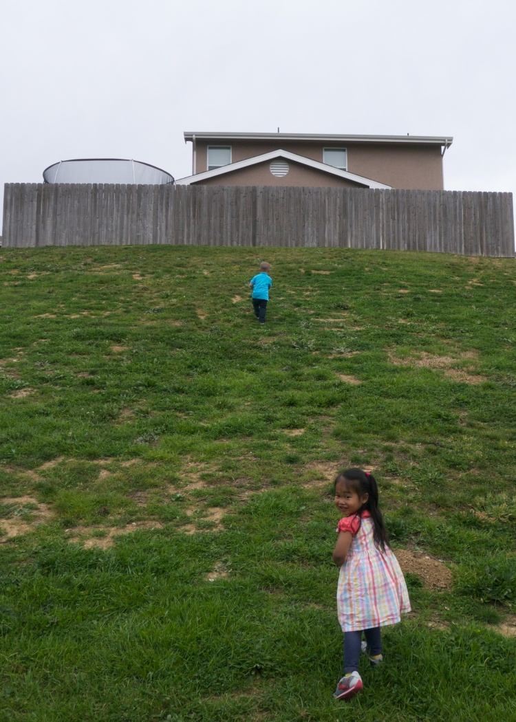Mia follows Kaleb up a hill during Kaiden's first birthday party.
